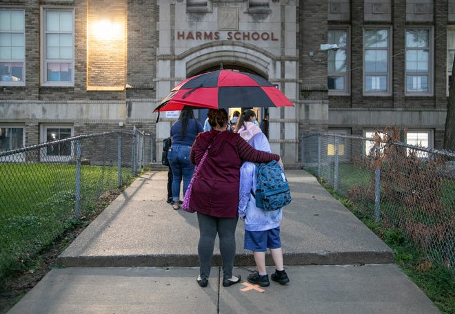 Claudia Gutierrez, of River Rouge, left, stands in the rain with her son Raul Gutierrez, 8, who will be starting the third grade at Harms Elementary School in Detroit Tuesday, Sept. 8, 2020.