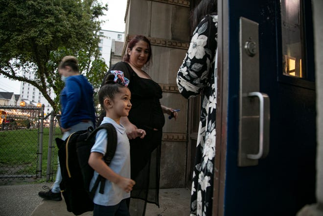 """Gianna Padilla, 5, all smiles, stands with her mother, Angelia Suppon, as they wait in the rain as Padilla heads to kindergarten at Harms Elementary School on Tuesday. """"I am so disappointed I can't go in with my daughter on her first day,"""" said Suppon."""