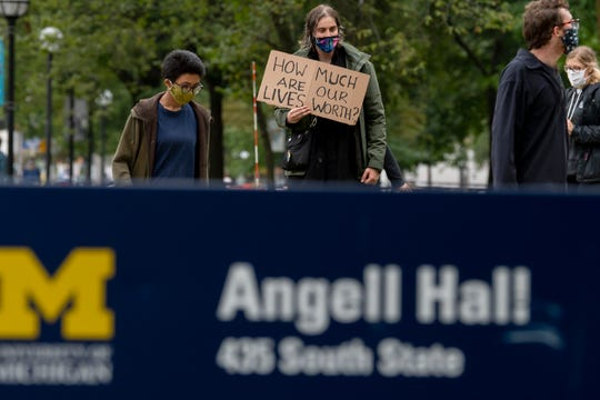 Abigail Finlay, center, a University of Michigan mathematics graduate student instructor, marches with fellow protestors in front of the University of Michigan's Angell Hall on State Street in Ann Arbor, Tuesday.