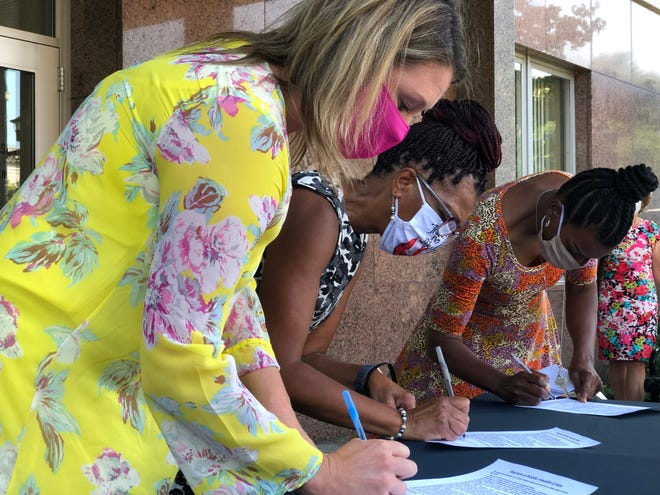 Wello Executive Director Natalie Bomstad, left, is joined by Brown County United Way's Robyn Davis, center, and YWCA Greater Green Bay's Renita Robinson as they sign the Racism as a Public Health Crisis Declaration on Aug. 26 outside of Green Bay City Hall.