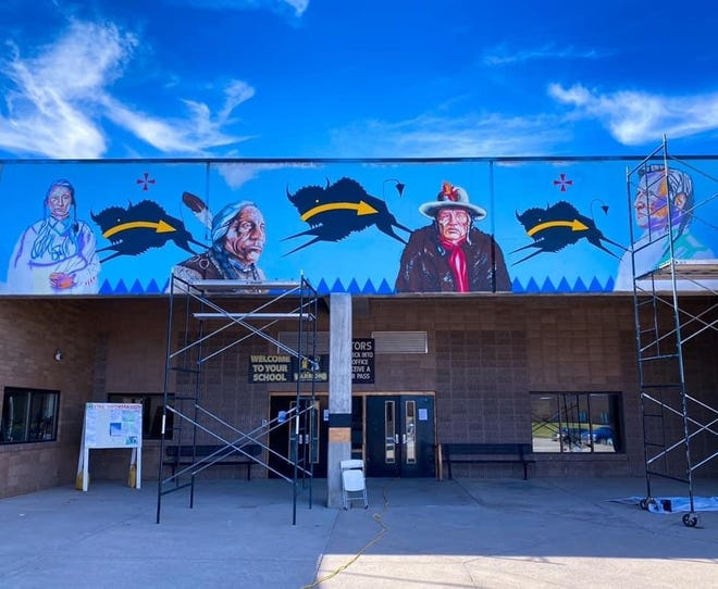 Artists John Pepion and Louis Still Smoking painted this mural, which features four Indigenous leaders, outside of Heart Butte High School.