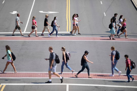Students cross Cumberland Avenue and Volunteer Boulevard on the University of Tennessee campus in Knoxville on Tuesday. The school has seen a recent uptick in coronavirus cases.