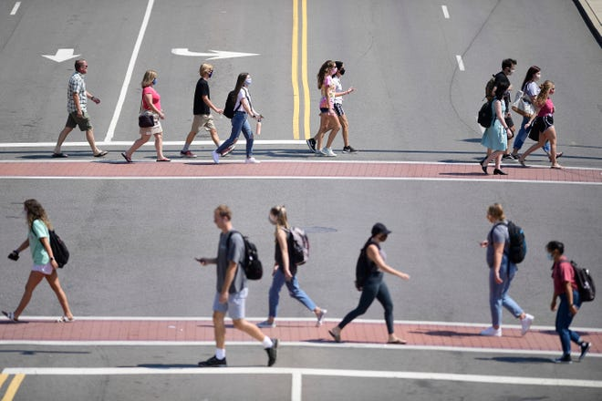 Students cross Cumberland Avenue and Volunteer Blvd. on the University of Tennessee campus in Knoxville, Tenn. on Tuesday, Sept. 8, 2020. The school has seen a recent uptick in coronavirus cases.