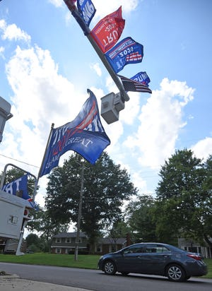 A driver passes under a bucket truck decorated with Trump 2020 flags on Rosedale Drive.