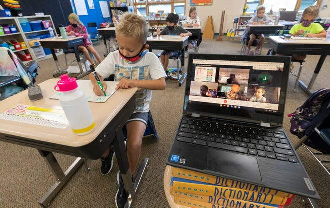 Second grade student Mason Fiore does classwork while next to a laptop with the images of students working at home in teacher Jennifer Kumlien's class Sept. 4, 2020, at Lake Country School in Hartland. Area districts that are conducting school in person are offering a virtual option as well.