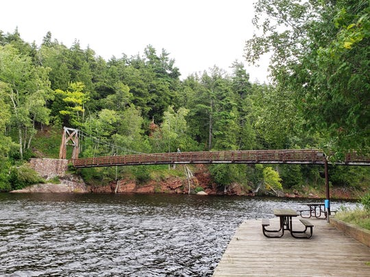 A 210-foot suspension bridge built by the CCC in 1939 crosses the Black River at Black River Harbor Recreation Area on Lake Superior in Michigan's Upper Peninsula.