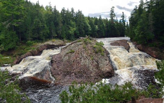 A large conglomerage rock separates the twin cascades of Great Conglomerate Falls on the Black River in the Ottawa National Forest in Michigan's Upper Peninsula.