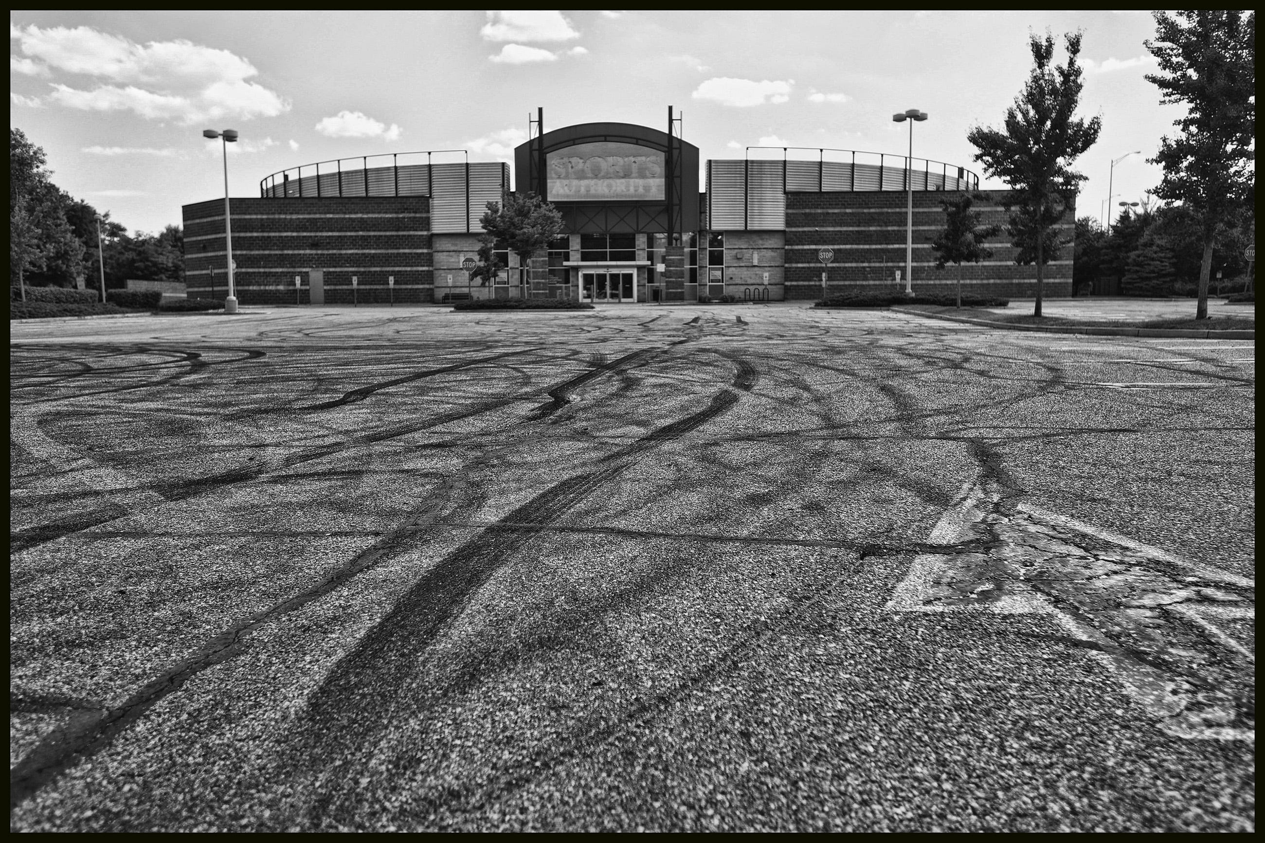 Traces of skid tires are seen on the front parking lot of the long time closed store Sport Authority in Paramus .