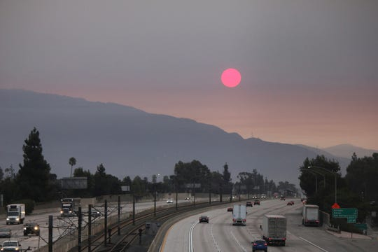 Smoke from wildfires burning east of Los Angeles dims the sunrise on Monday, Sept. 7, 2020, seen from Pasadena, Calif. The Bobcat Fire was burning near Cogswell Reservoir in the San Gabriel Mountains while the El Dorado Fire consumed thousands of acres of vegetation near the community of Yucaipa on the foothills of the San Bernardino Mountains.