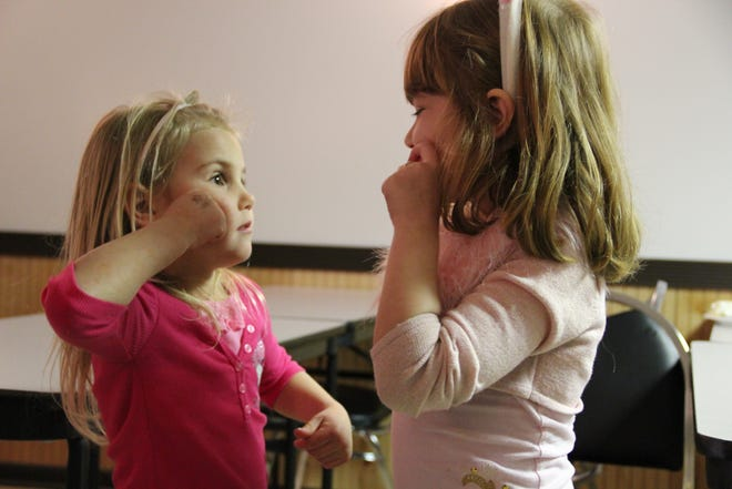 Two young girls communicate via sign language.