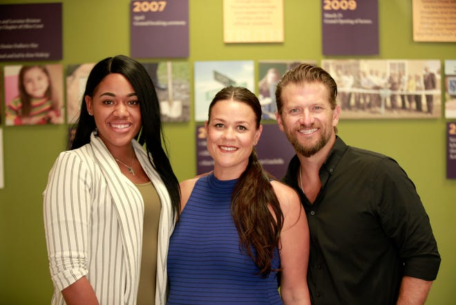 Tatyanna Voorhies, community involvement coordinator for Olive Crest, poses with Lanay and Justin Berry, owners of Caritas Realty.