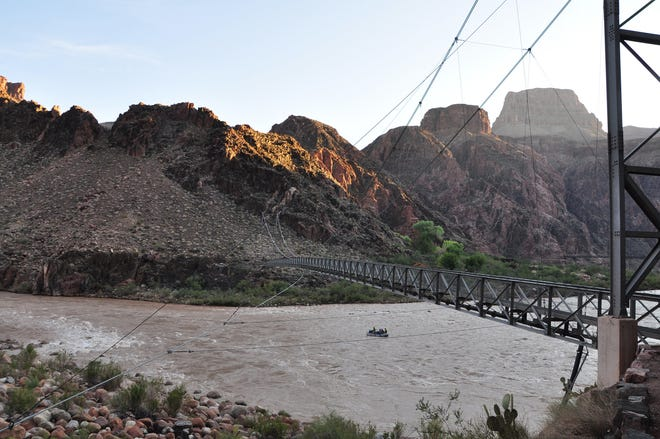 Boaters on the Colorado River pass under the Silver Bridge while getting an early start on their day's journey.