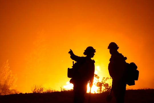 Members of the Laguna Hotshots, out of the Cleveland National Forest, make a stand on a hilltop near a power station while fighting the Creek Fire, Sunday, Sept. 6, 2020, in Big Creek, Calif.