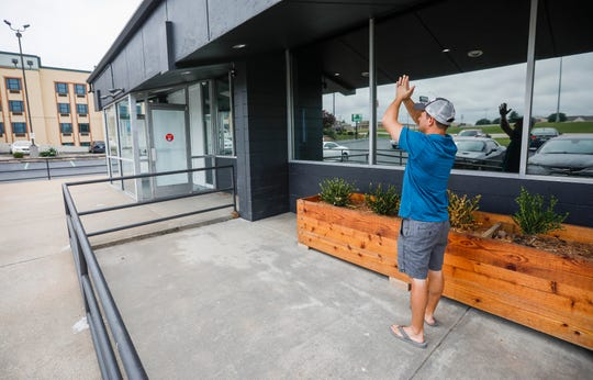 John Lopez, owner of Old Route 66 Wellness, demonstrates how the artificial intelligence security system at the front entrance of the medical marijuana dispensary works.
