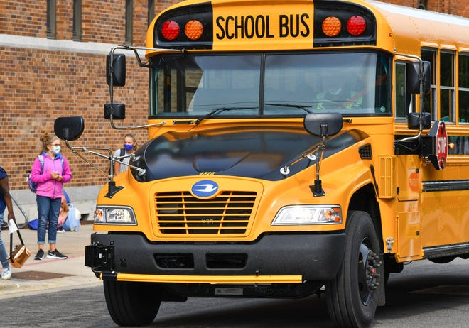 Busses stop outside Cathedral High School after classes Tuesday, Sept. 8, 2020, in St. Cloud.