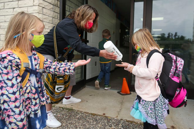 Julie Miskoski provides hand sanitizer for students as they enter the building on Sept. 8 at McKinley Elementary School in Stevens Point. Many schools that opened to in-person instruction have since had to close again because of COVID-19 cases at the school and in their communities, and staffing challenges have been exacerbated by the high number of staff members in quarantine.