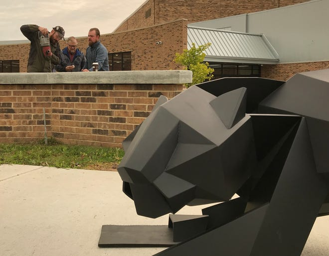 August, Boleslaw and Vincent Kochanowski work together to install the new SPASH panther on its brick and concrete pedestal. August designed the piece, and fabricated with the help of his father, Boleslaw, and brother, Vincent.