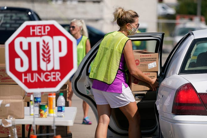 A volunteer loads a local resident's vehicle at a drive-up produce giveaway organized by a Des Moines food pantry, Friday, Aug. 28, 2020, in Des Moines, Iowa. The effort began in the spring when efforts to slow the spread of the coronavirus caused food demand at restaurants and schools to plunge, leaving farmers with little choice but to dispose of produce, meat and dairy products even as millions of people desperately turned to help from overwhelmed food banks.