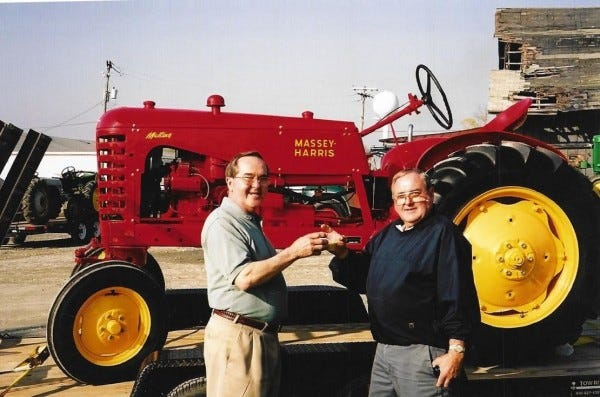 Newell Jr., left, and Spencer Everett raise a toast to their father's refurbished tractor, which they recently donated to the Delaware Agricultural Museum and Village. (Submitted photo)