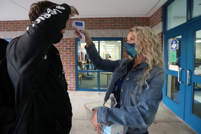 Biology teacher and intervention specialist Kelly Brock takes a student's temperature on the first day of school at Zanesville High School on Tuesday.