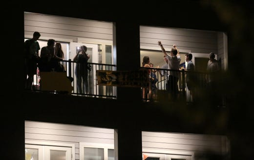 Partiers congregate on the balcony of a downtown apartment on Tuesday, Sept. 1, 2020, in Columbia, Mo., near the University of Missouri campus. Many colleges quickly scrapped in-person learning in favor of online after cases began to spike, bars have been shut down in college towns, and students, fraternities and sororities have been repeatedly disciplined for parties and large gatherings.