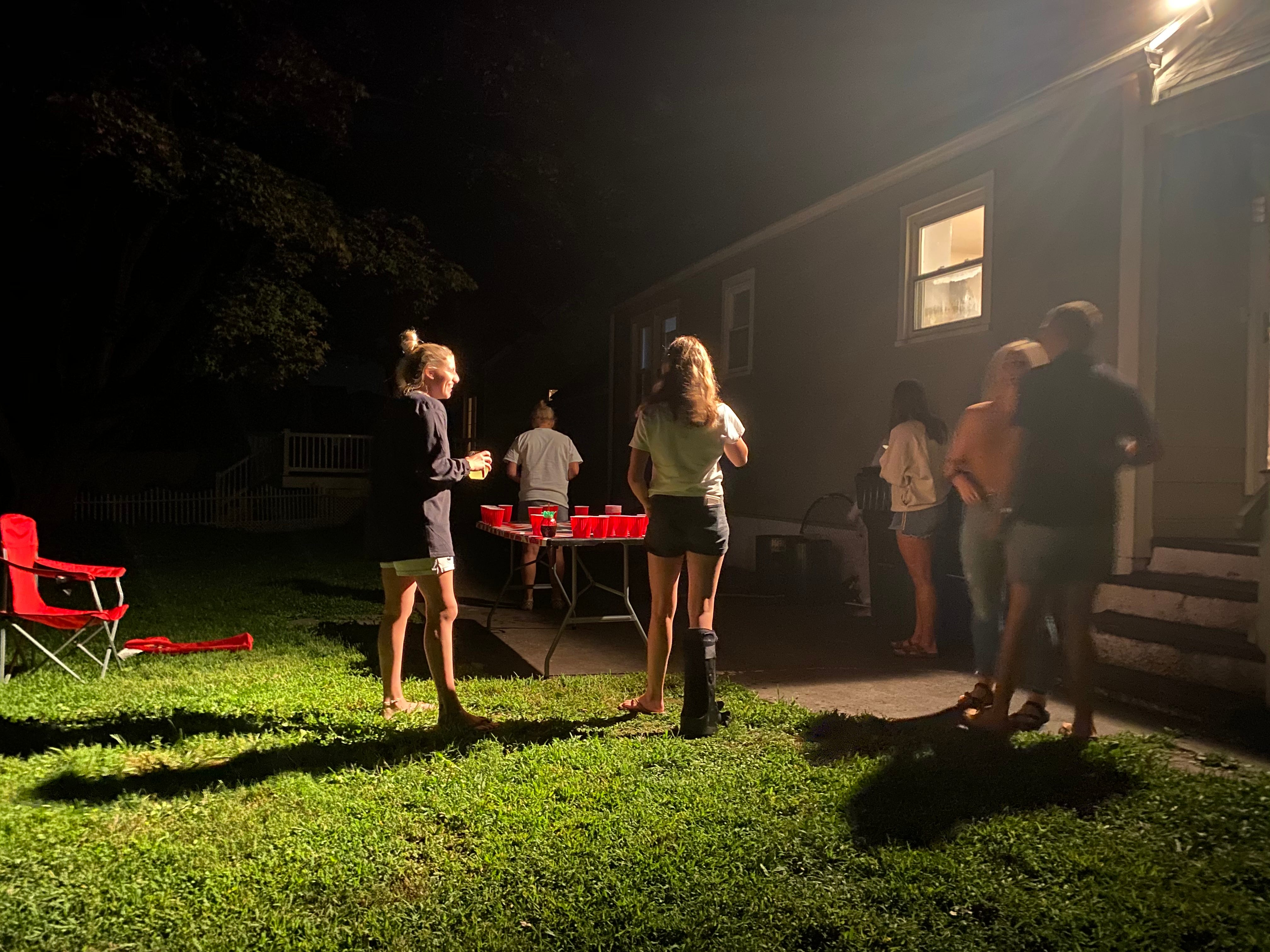 People congregate Friday at a party near the Fairfield University campus in Connecticut. A prior version of this story misstated the credit for this photo.