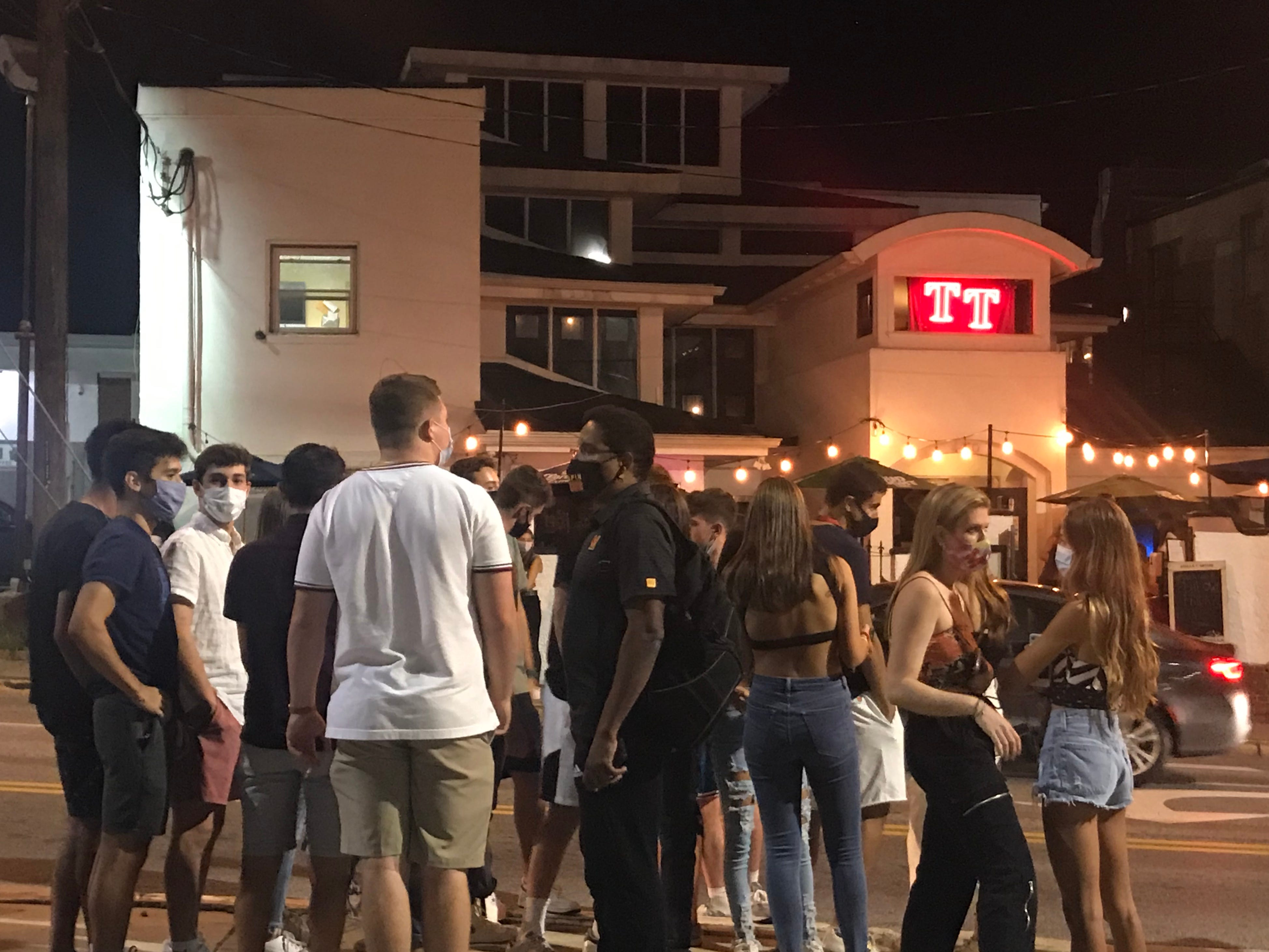 """""""Put your masks on!"""" a student called when University of Maryland President Darryll Pines, center, wearing black, stopped by a gathering near campus on Friday night."""