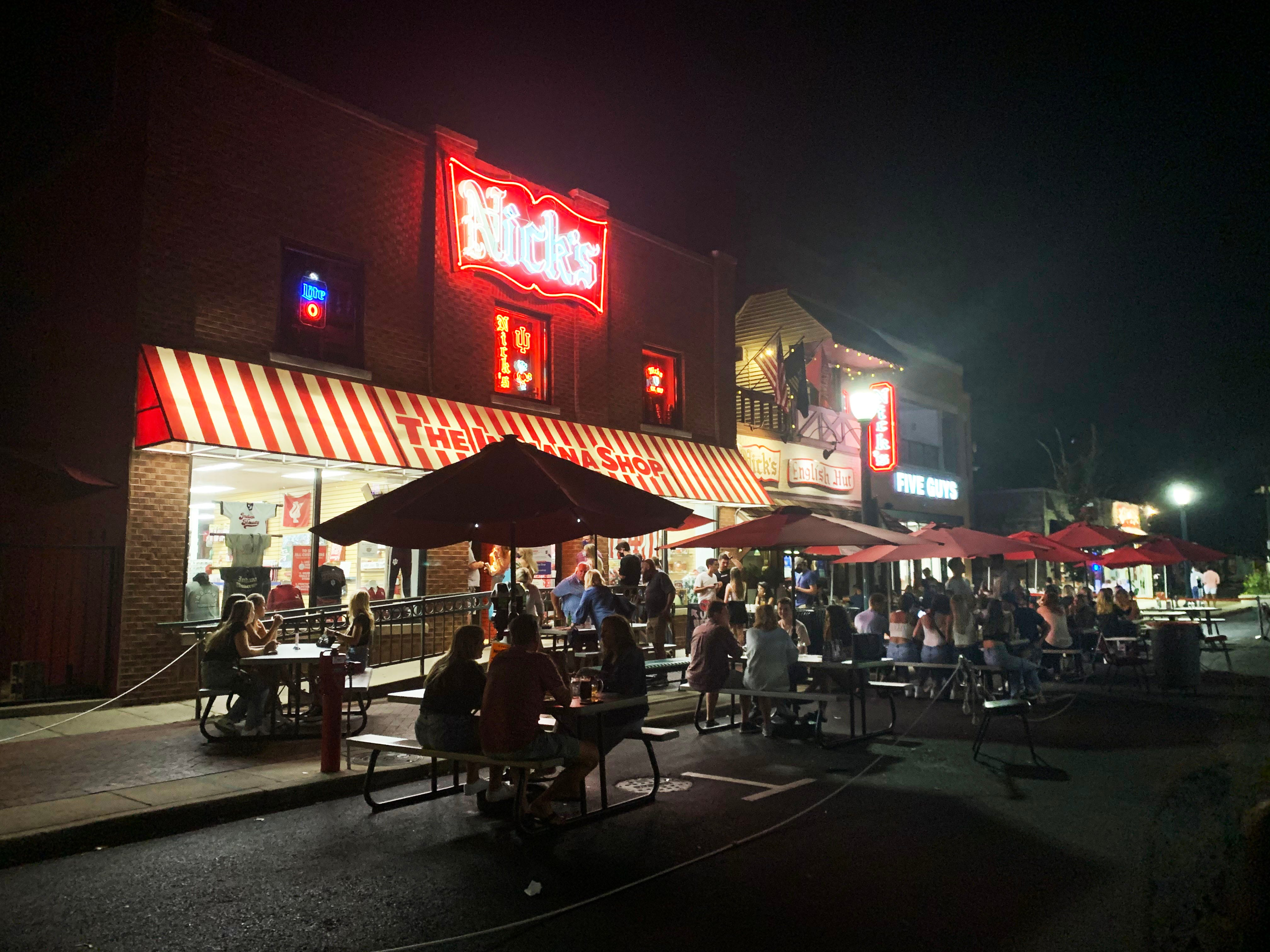 People congregate Thursday outside Nick's bar in Bloomington, near the Indiana University campus.