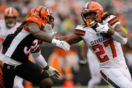 Cleveland Browns running back Kareem Hunt (27) stiff arms Cincinnati Bengals strong safety Shawn Williams (36) on a carry in the fourth quarter of the NFL Week 17 game between the Cincinnati Bengals and the Cleveland Browns at Paul Brown Stadium in downtown Cincinnati on Sunday, Dec. 29, 2019.