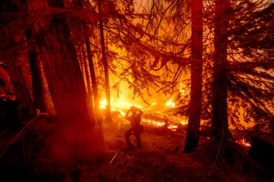 A firefighter battles the Creek Fire in the Shaver Lake community of Fresno County, Calif., on Monday, Sept. 7, 2020.