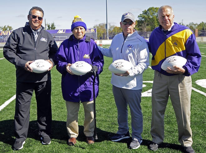 From left to right, assistant coach John Saccomen, former head coach Fred Martinelli, head coach Lee Owens and former head coach Gary Keller pose with game balls commemorating the Ashland University football program's 500th victory, which came on Sept. 28, 2019 against Northwood. The photo was taken Oct. 12, 2019 before the game against Davenport.