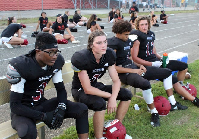 Taking a break on the sidelines, from left, #3 freshman Amontae Austin, #7 junior Weston Bockelman, #1 senior Lamarius Martin and #12 senior Charlee Winchester.
