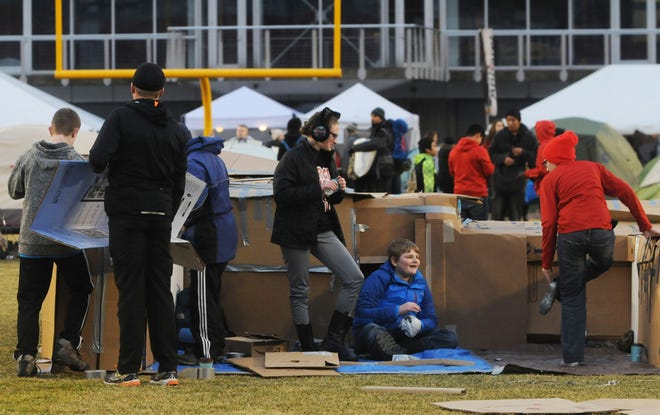 Members of Story City Methodist Church youth group make shelter with cardboad boxes during a 2017 Reggie's Sleepout event at Jack Trice Stadium in Ames.