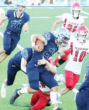 Bartlesville High School rst-year starting tailback Caleb Perry, center, powers past a would-be tackler during last the Sept. 4 football opener against Claremore. Perry averaged more than 27 yards a carry to accumulate 137 yards during a half-night's work.