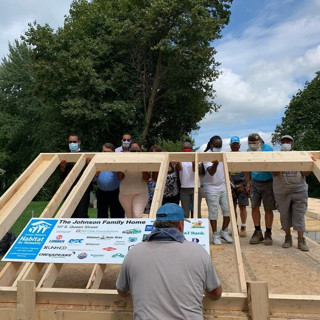 Volunteers, the Johnson family and members of the community raise a wall of the new home on South Queen Street Sept. 2.
