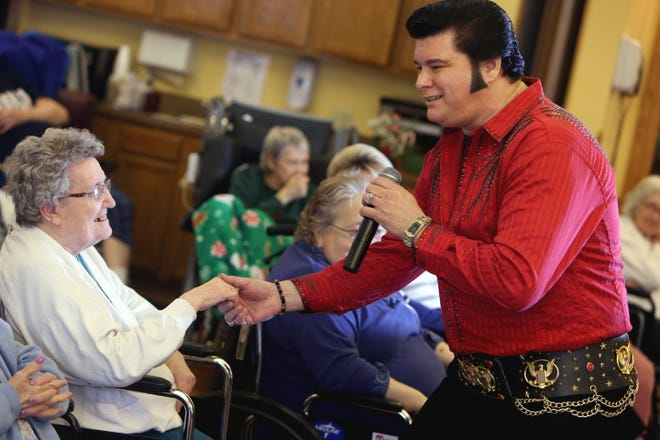 Elvis impersonator Junior Talley holds Betty Ingle's hand while entertaining the residents at the Oak Lane Nursing & Rehab facility in Stronghurst, Illinois. Junior Talley will perform from 1 to 3 p.m. Saturday at Steamboat Senior Center, 501 Jefferson Street.
