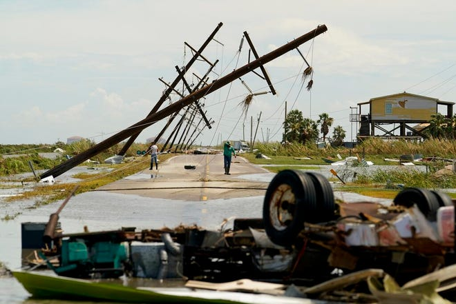 In this Aug. 27, 2020, file photo, people survey the damage left in the wake of Hurricane Laura in Holly Beach, La. A hotter world is getting closer to passing a temperature limit set by global leaders five years ago and may exceed it in the next decade or so, according to a new United Nations report released on Wednesday.