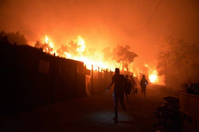 Refugees and migrants run as fire burns in the Moria refugee camp on the northeastern Aegean island of Lesbos, Greece, on Wednesday. Fire Service officials said a large refugee camp on the Greek island of Lesbos has been partially evacuated despite a COVID-19 lockdown after fires broke out at multiple points around the site early Wednesday.