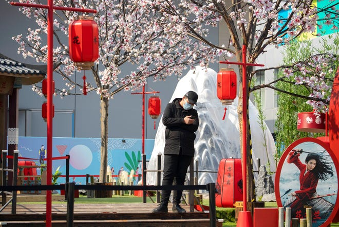 """In this Feb. 19, 2020, photo, man stands in a set promoting the Disney movie """"Mulan"""" in Beijing. Disney is under fire for filming part of its live-action reboot """"Mulan"""" in Xinjiang, the region in China where the government has been accused of human rights abuses against Uighurs and other predominantly Muslim minorities."""
