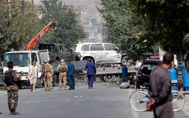 Afghan security personnel move damaged vehicles belonging to a vice presidential convoy targeted by an explosion in Kabul, Afghanistan, on Wednesday. A spokesman for Afghanistan's Interior Ministry said the bombing that targeted the convoy of the country's first vice president on Wednesday morning killed several people and wounded more than a dozen others, including several of the vice president's bodyguards.