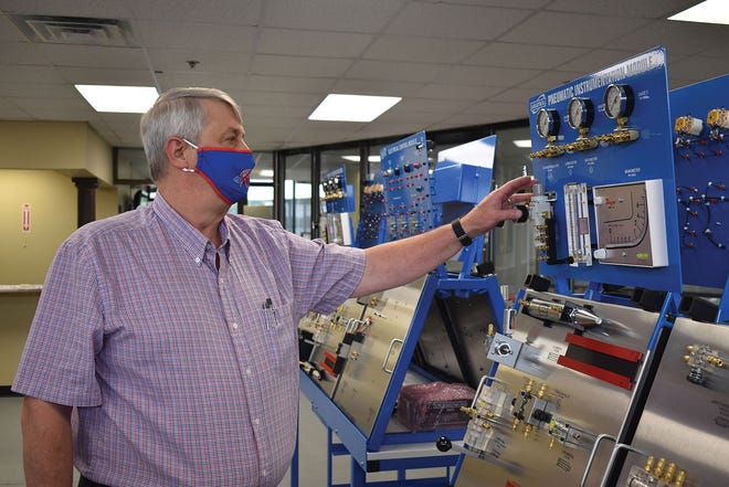 Wearing a Roane State-branded face mask, Gordon Williams, director of the community college's mechatronics program, assembles a component of the new lab in part of the Learning Center on the Roane County campus.