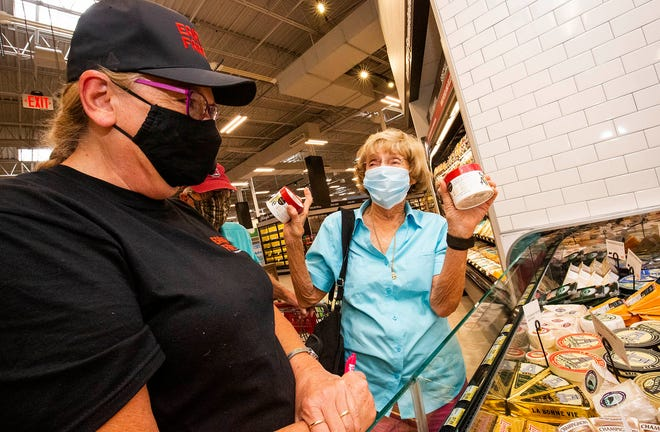 """Mary Galloway, right, was excited to see that Earth Fare, a natural food supermarket, had reopened Wednesday at the Shady Oaks Shopping Center. """"This is my favorite cheese,"""" Galloway said as Rebecca Brandt helped Galloway find her cheese. In February, the original chain filed for bankruptcy and announced it would shutter all 50 of the stores across the country. The store is now owned by a group led by Dennis Hulsing."""