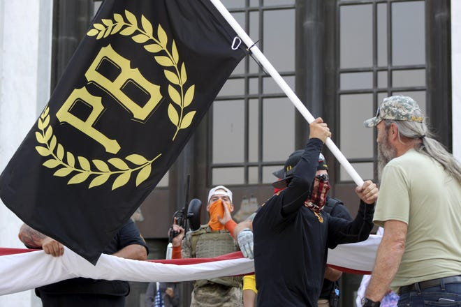 A protester carries a Proud Boys banner, a right-wing group, while other members start to unfurl a large U.S. flag on Sept. 7 in front of the Oregon State Capitol in Salem. The protester at center is holding a paintball gun. Hundreds of people gathered on Labor Day in a small town south of Portland for a pro-President Donald Trump vehicle rally, just over a week after member of a far-right group was fatally shot after a Trump caravan went through Oregon's largest city. Later, pro-Trump supporters and counter-protesters clashed at Oregon's Capitol.