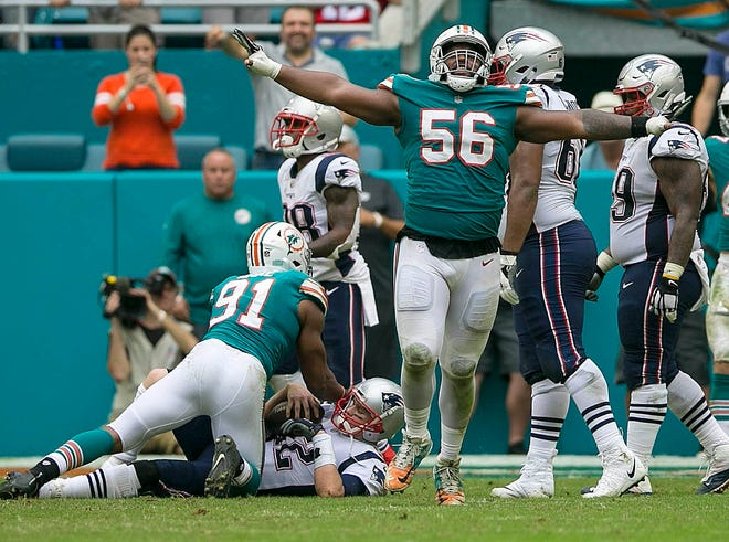 Miami Dolphins defensive tackle Davon Godchaux (56), celebrates after his teammate Miami Dolphins defensive end Cameron Wake (91), sacked New England Patriots quarterback Tom Brady (12), during second half action of their NFL game Sunday Dec. 9, 2018, in West Palm Beach. [BILL INGRAM/palmbeachpost.com]
