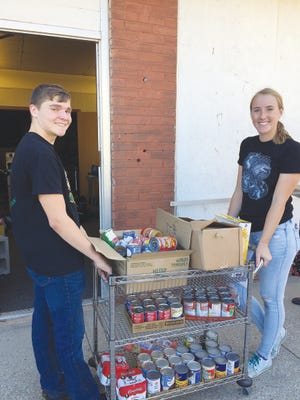 Pratt students Andrew VanSlyke and Ruby Howell help deliver canned goods to the Pratt Food Bank during last year's PHS StuCo. food fundraiser.