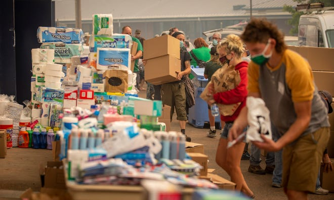 Volunteers attend to donations for distribution to those who have been displaced by the Holiday Farm Fire. The Springfield City Council voted Monday to allow evacuees to temporarily live in RVs parked on residential property.