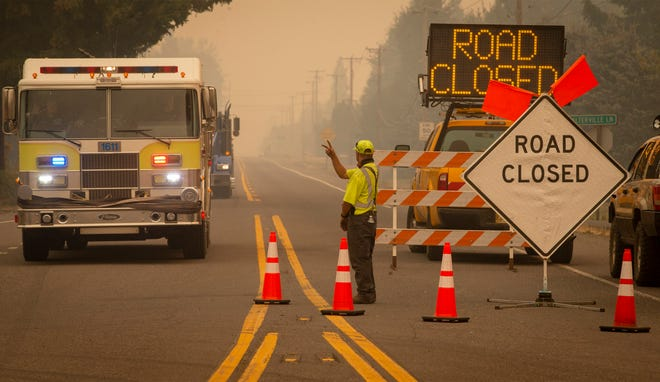 An Oregon Department of Transportation worker acknowledges a truck from the McKenzie Fire District as it passes a roadblock outside Springfield on Sept. 9.