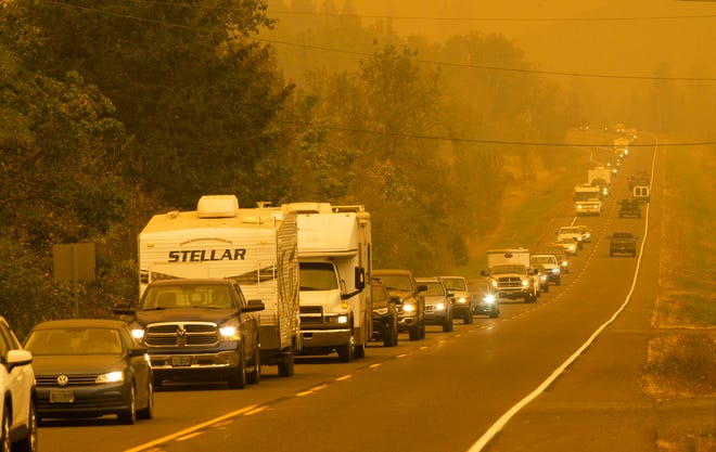 Vehicles make their way west on Marcola Road as residents evacuate the area ahead of a fast-moving wildfire Tuesday.