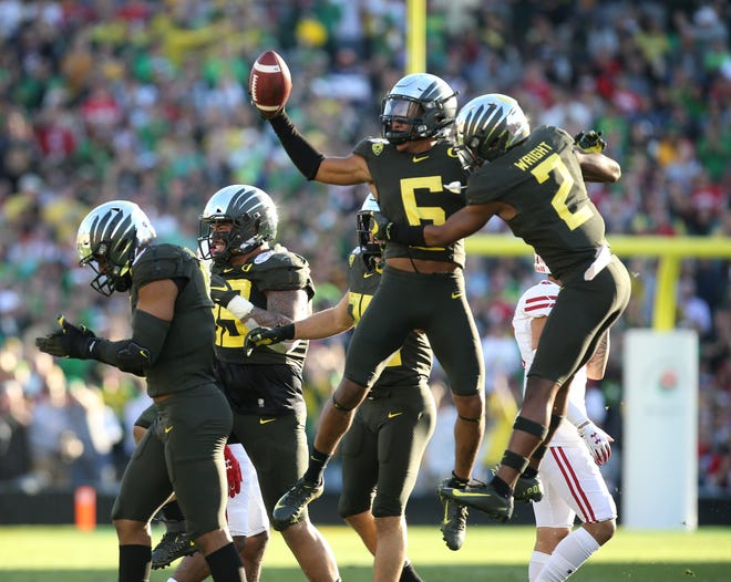 Oregon's Deommodore Lenoir, center, celebrates a first-half fumble recovery in the Ducks' 28-27 Rose Bowl win against Wisconsin. [Chris Pietsch/The Register-Guard] - registerguard.com