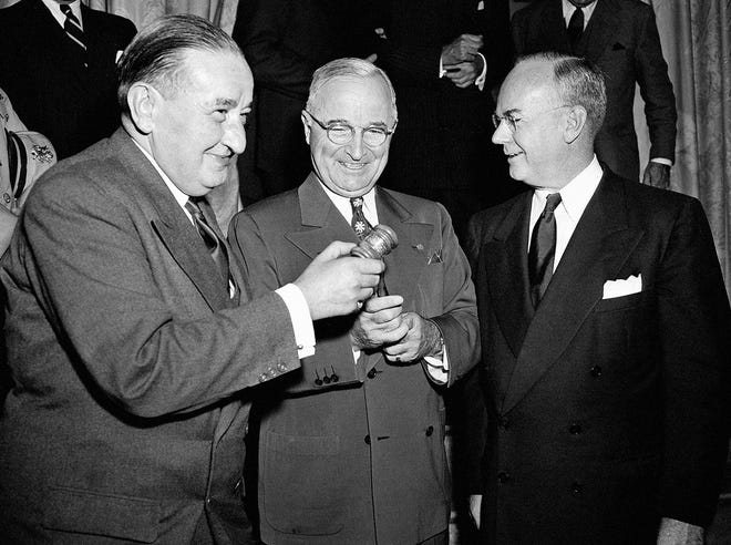 """President Truman (center) receives from Maurice Petsche (left), French Finance Minister, a gavel at a meeting of the International Monetary Fund and World Bank governors in Washington, on Sept. 13, 1949. The president appealed to 48 member nations to """"Do away with the obstacles to international trade."""" Secretary of the Treasury John Snyder (right) represents the United States in both groups. The gavel was made from a tree from Bretton Woods, N.H., where international agreements were reached in 1944 to found the World Bank and International Monetary Fund."""